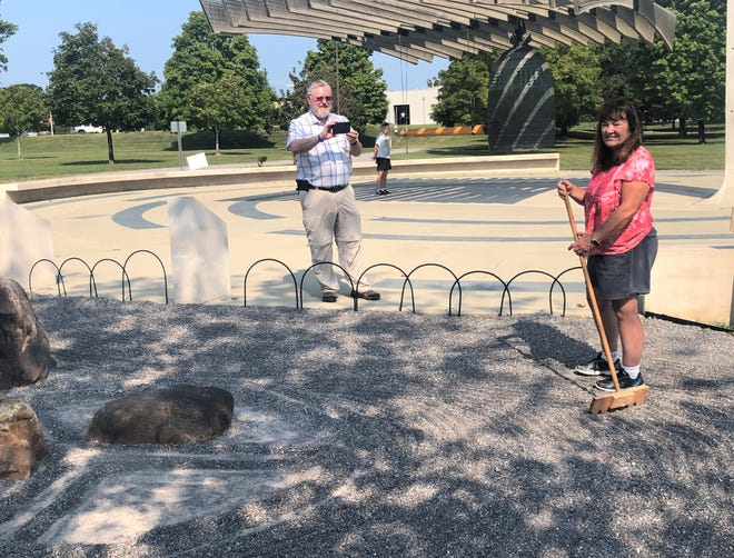 """Debbie Cutler, right, prepares the karesansui garden with a """"Gardens for Peace"""" design for the Sept. 21 International Day of Peace, while Ray Smith videos Cutler and the garden for a presentation to the North America Japanese American Garden Association. Cutler and Lucky Vogt, who is preparing to ring the International Friendship Bell, are volunteer gardeners who rake designs in the gravel garden."""