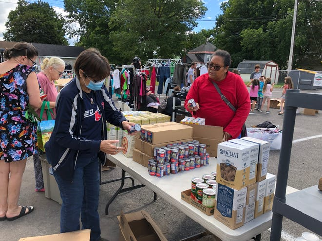 """Sandy Payne, of Rome, and Esther Clinton, of Rome, look over the free groceries , clothing and other items on offer by Connected Community Schools on Sept. 3.  The nonprofit held the impromptu """"sale"""" in the DeSalvo Catering and Restaurant parking lot on North James Street to help out victims of recent flooding and others, and to clear out for sister's grandkids using some of the goods it had stored in the now closed George R. Staley Elementary School."""