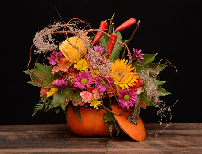 For a festive fall centerpiece, try hollowing out a pumpkin. Drop in a plastic liner or a glass vase filled with floral foam. Fill the foam with seasonal flowers, branch material, Spanish moss and dried peppers or pepper berries. Prop the pumpkin top against the arrangement as a finishing touch.