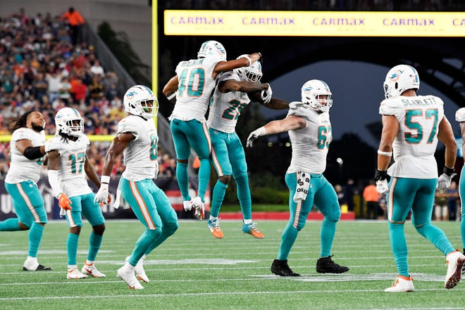 Miami Dolphins defensive back Nik Needham (40) celebrates with cornerback Xavien Howard (25) and teammates after a turnover by the New England Patriots during the second half at Gillette Stadium. Brian Fluharty-USA TODAY Sports
