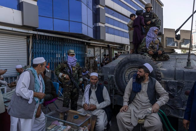 Taliban fighters guard a money exchange in Kabul, Afghanistan, Aug. 26, 2021. Only a fraction of those Afghans wary of the Taliban managed to be evacuated. Many of the rest are now in hiding, worried for their safety and their future.