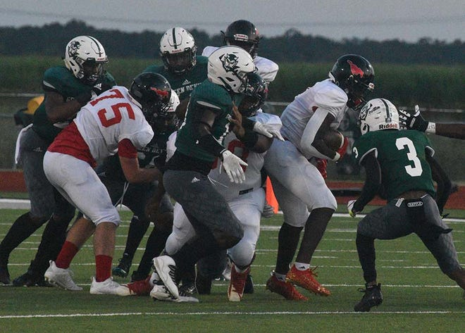 Plaquemine's Shermar Carter tries to find his way through a wall of Assumption Pioneers in action last Friday at Andrew Canova Green Devil Stadium.
