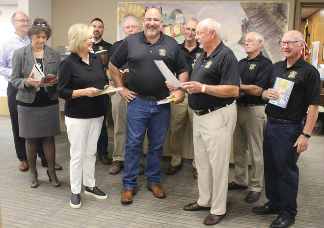 With books in hand, members of the Pratt Rotary Club join in a special presentation on National Literacy Day on September 8 at the Pratt Public Library, led by Pratt Rotary President Darrell Shumway (front, right). Rotary service committee chairperson Suzan Patton (front, left) gave Pratt Library Director Eric Killlough (front, middle) a check for more than $1,500 in support of the library's literacy efforts. Others pictured include (front, left to right) Donna Meier Pfeifer, Patton, Killough, Shumway, Steve LaPrad, and (back)  Jack Galle, Mark Graber, Tom Jones, Gary Skaggs and Don Hommertzheim.