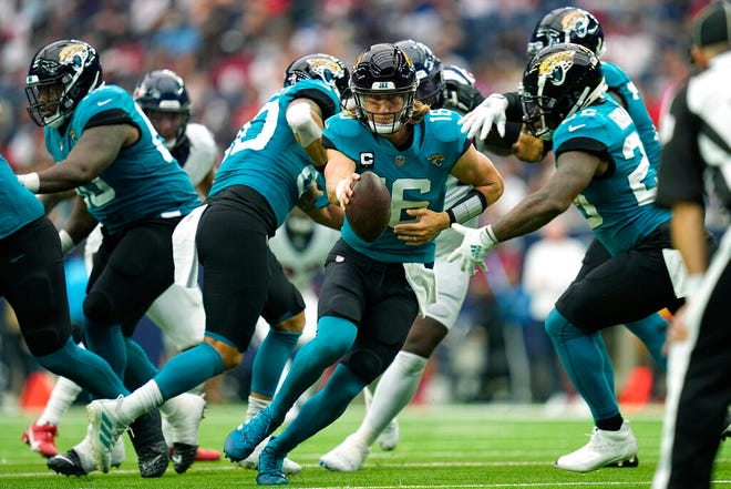 Jacksonville Jaguars quarterback Trevor Lawrence (16) reaches to hand the ball off to running back James Robinson, right, during their game against the Houston Texans Sunday, Sept. 12, 2021, in Houston.