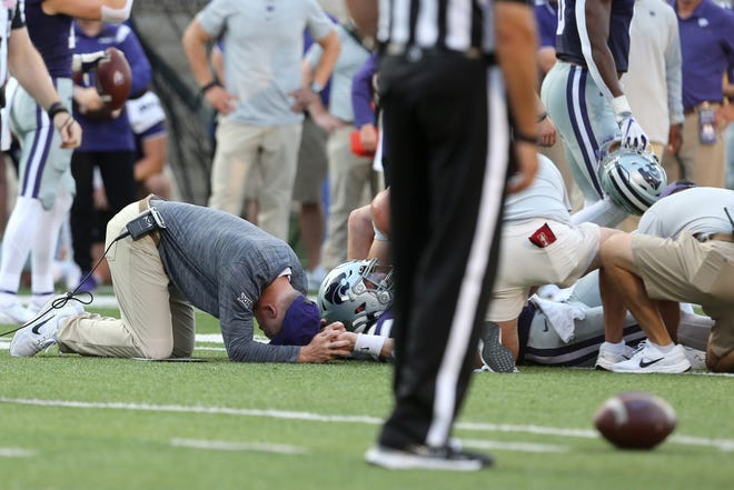 Kansas State coach Chris Klieman, left, holds the hand of injured starting quarterback Skylar Thompson (7) as medical personnel tend to him on Saturday.