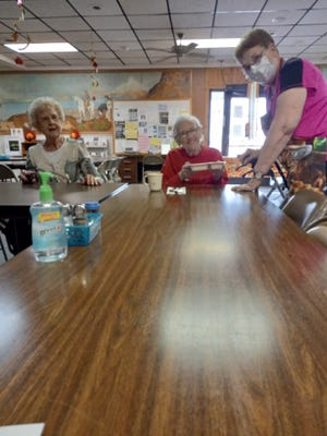 Hays Nutrition Site Manager Vickie Thyfault, right, serves meals to Peggy Brungardt, center, and Millie Rohr, left. The NorthWest Kansas Area Agency on Aging provides more than 16,500 meals a month in 18 counties with its nutrition project.