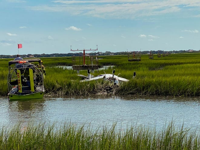 A rescue vehicle sits next to a plane in the marsh near the Northeast Florida Regional Airport after a wreck on Monday.