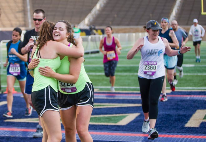 Elisabeth Casetti, left, and Megan Rach, both 17 at the time, hug after crossing the 10K finish line together in Notre Dame Stadium in the Sunburst Races in 2019. This year, finishers will need to pull aside and don a mask.