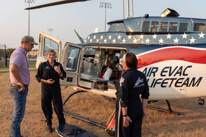 A crew from the Seminole Air Evac explain their operations to Governor Stitt after landing their helicopter at the First Responders dinner.