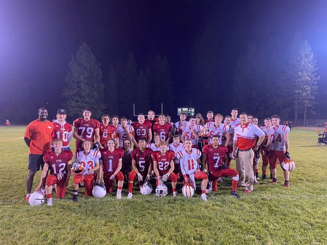The Etna Lions football team, in Red, pose for a photos with the Trinity Wolves squad after Saturday's game in Weed.