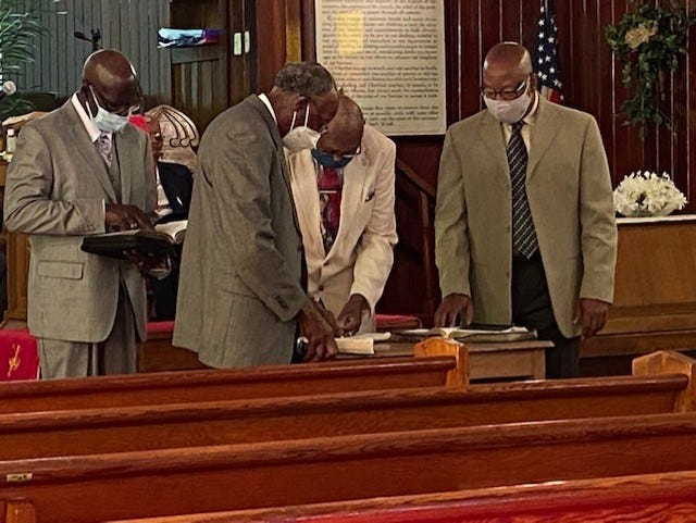 The deacons of Emanuel Baptist Church lead devotion during the Sunday morning worship service at the church.