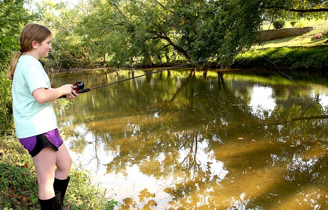 Jenna Livingston fishes in Leatherwood Creek Sunday evening. Livingston and her sister, Allison Livingston, (not pictured), were using redworms, with Allison catching a sunfish shortly before this picture was taken.