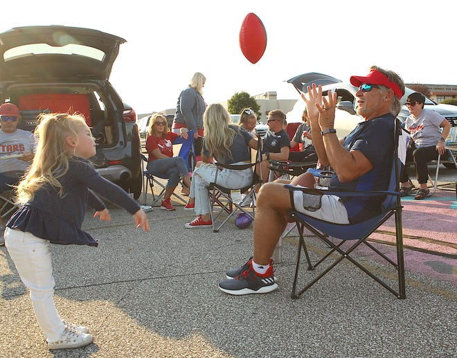 Thea Blackwell throws a football to her Grandfather, Kenny Dalton Friday evening in the BNL parking lot. The two were tailgating with family and friends before the start of BNL's game with HHC rival New Albany.