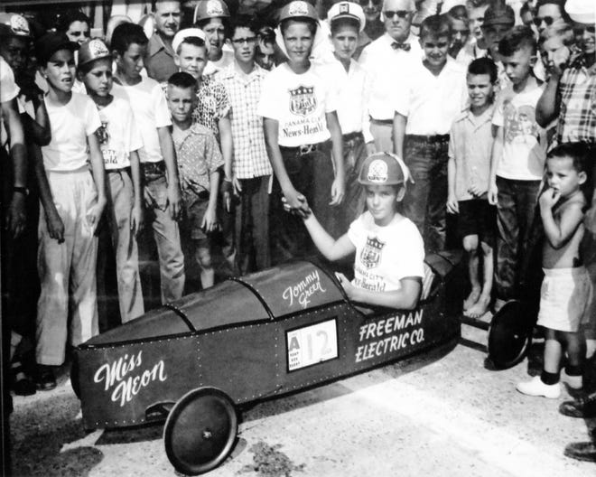 """Tommy Green, behind the wheel of """"Miss Neon,"""" is Panama City's first Soapbox Derby champion. Green is congratulated by first runner-up, Stanley Hobbs of DeFuniak Springs. Green won the right to represent Florida, Alabama and southern Tennessee in the All-American Soapbox Derby finals in Akron, Ohio, in 1954."""