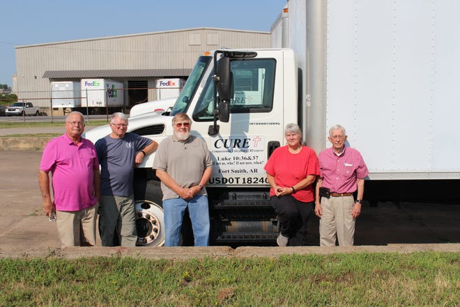Volunteers Ron Hamilton, John Mundy, Kevin Vaught, Nancy James and Mat Griffin stand outside one of CURE's warehouses, located at 2400 Vicksburg Ave. in Fort Smith.