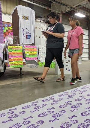 Jo and Jing Jing Sheffield walk laps Friday night at the 25th annual Brown County Relay For Life at the Holum Expo Building at the fairgrounds. The event is a fundraiser for the American Cancer Society. It concluded Saturday morning. The amount raised is not yet available.