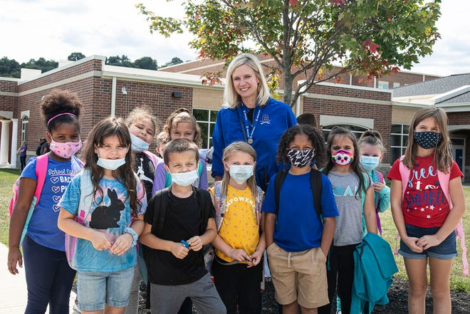 Newly chosen Kim Hurst poses with several primary students after school on Friday, Sept. 10, 2021. Hurst, a New York State native, started out as a music teacher in Rochester but followed her family to Ohio to continue teaching and is now the new principal for Chillicothe Primary, replacing long-time Chillicothe principal Joanna Strawser.