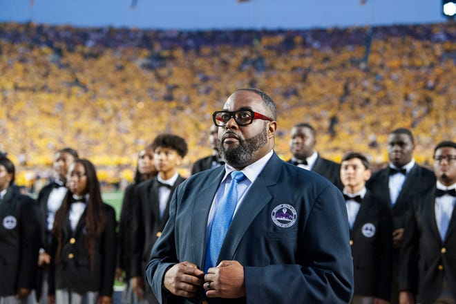 """Director Anthony White gets ready to lead The Detroit Youth Choir as they perform """"God Bless America"""" before a crowd of more than 108,000 fans at the Michigan vs. Washington football game at Michigan Stadium in Ann Arbor."""