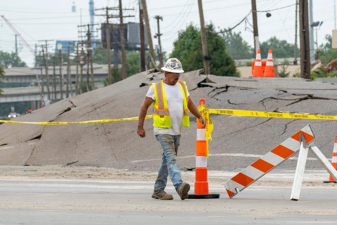 Un travailleur passe devant un monticule qui a bouillonné au milieu de la rue Dearborn, près de la rue Fort, le 13 septembre 2021, après qu'une rupture de conduite d'eau a endommagé la rue ainsi qu'une entreprise voisine la veille.