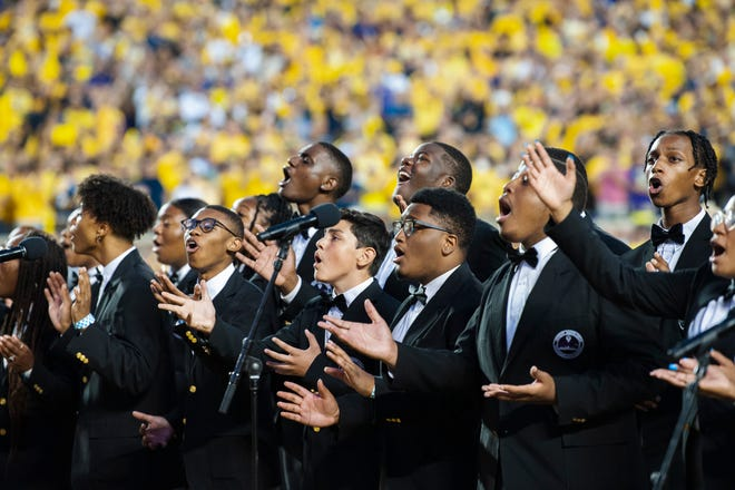 """The Detroit Youth Choir performs """"God Bless America"""" for a crowd of more than 108,000 fans before the Michigan's 31-10 victory over Washington at Michigan Stadium in Ann Arbor."""