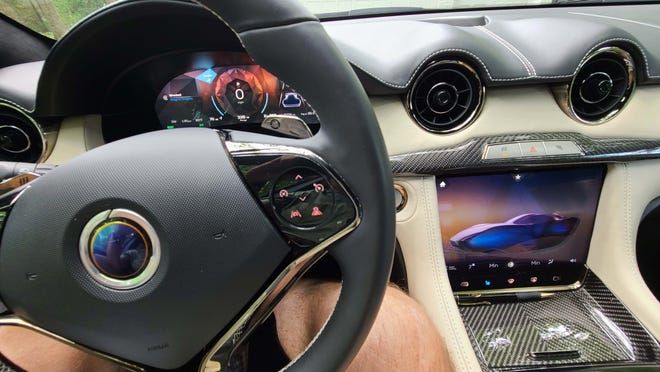 The retro cockpit of the 2021 Karma GS-6 includes update screens and steering wheel controls.