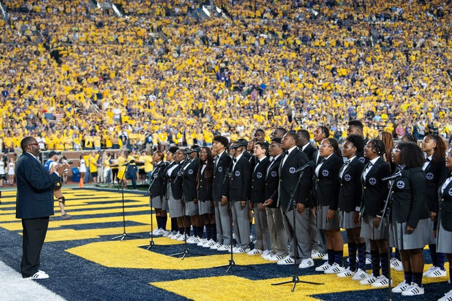 """Director Anthony White, left, leads The Detroit Youth Choir as they perform """"God Bless America"""" before a crowd of more than 108,000 fans at the Michigan vs. Washington football game at Michigan Stadium in Ann Arbor."""