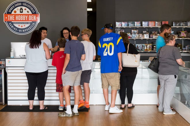 Les gens achètent des cartes de sport au Hobby Den à Evansville, Indiana, samedi après-midi, 11 septembre 2021.