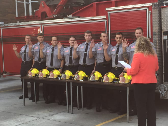 Mansfield Safety-Service Director Lori Cope swears in eight new firefighters Monday morning.