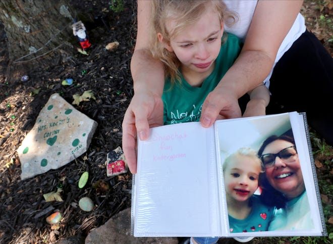 Amand Switalski holds a photograph of her daughter Charlotte Switalski, 7, and Susan Keener, Charlotte's special needs teacher aid at Walter Hill School that passed from COVID.  The two are seated next to a garden dedicated to Keener at the school.