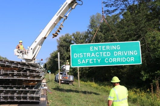 Workers install new safety alert signs on the expressway between Granville and New Albany in Licking County. The new zero-tolerance enforcement safety zone spans 12 miles between the two communities.