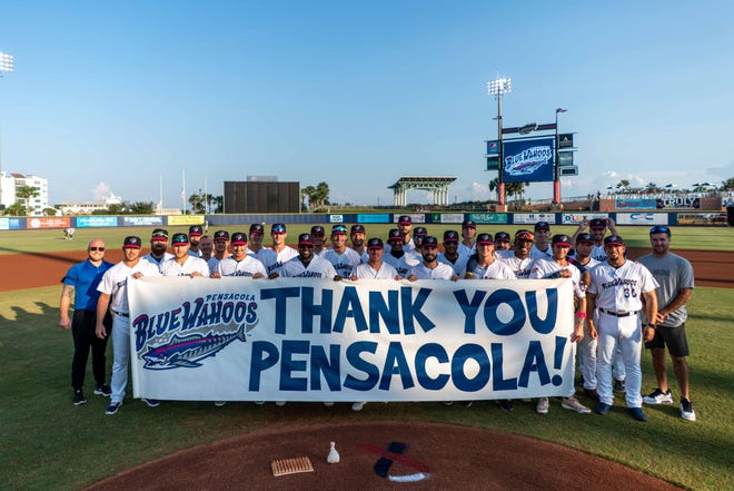 Blue Wahoos players and coaches are joined by Bubba Watson, far right, with banner thanking fans for their support in 2021, prior to their Sept. 11 game against the Biloxi Shuckers.
