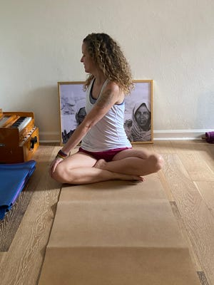 Ana Mares-Guia demonstrates a pose: Exhaling fully, twist towards your left shoulder.