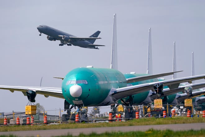 A U.S. Air Force KC-46A Pegasus jet takes off in view of a line of Boeing 777X jets parked nose to tail on an unused runway at Paine Field, near Boeing's massive production facility in Everett, Wash.