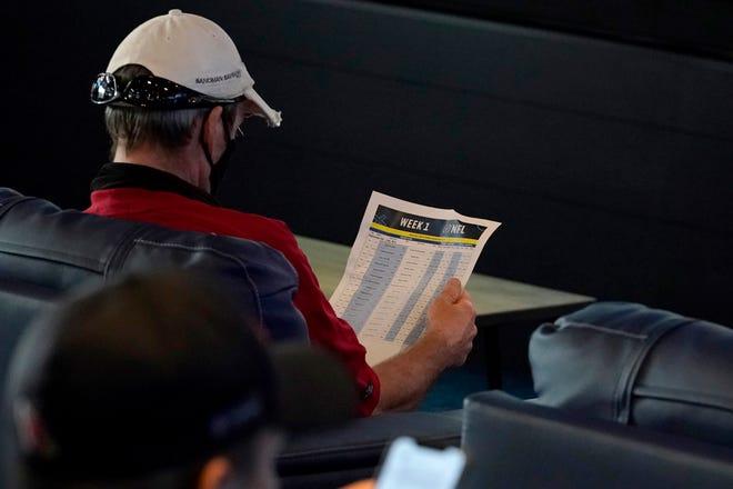 A customer looks over NFL matchups inside FanDuel Sportsbook at the Footprint Center in Phoenix.