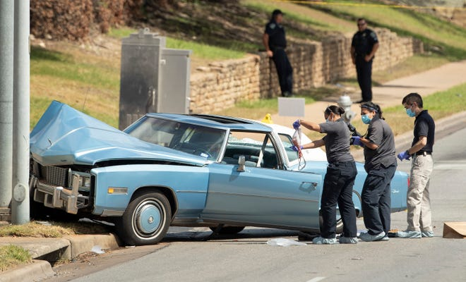 An Austin police crime scene investigator holds up a piece of bloody clothing while investigating a homicide Tuesday in the intersection of Cameron Road and Rutherford Lane.