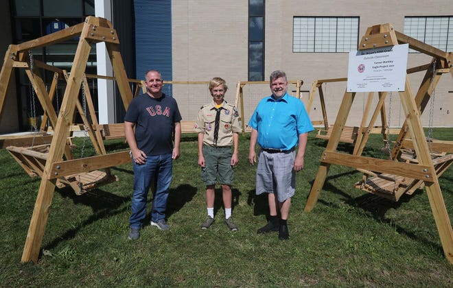 Chad Nash, left, STEM instructor at Tallmadge Middle School; Tanner Markley of Boy Scout Troop 361; and Jon Bryan, a fifth grade teacher at Tallmadge Elementary School stand in front of Tanner's Eagle Scout project at the elementary school. The circle of swings is the first of several proposed outdoor classrooms and a learning trail that will be funded by a GAR grant.