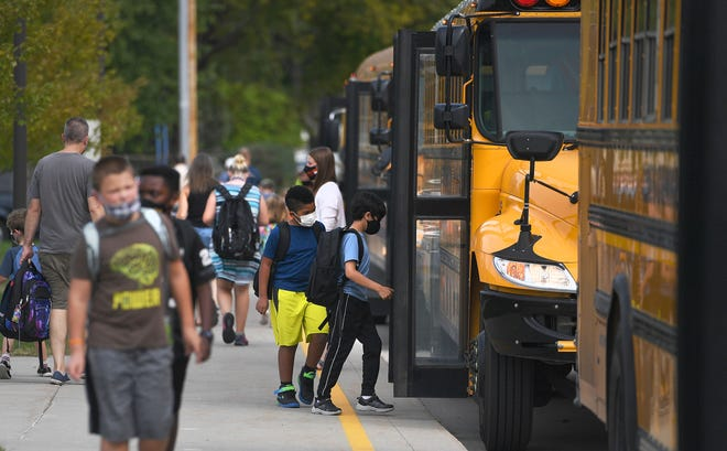 Fellows Elementary students walk home with their parents after school is dismissed Monday, Sept. 13, 2021, in Ames, Iowa.