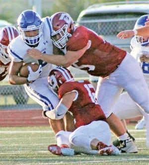 Dewey High School's defense buries a Miami Wardog ballcarrier during Week One action.