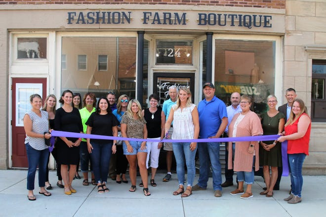 A ribbon cutting was held at Fashion Farm Boutique, 24 E. Fort St., in August. Lisa Deppermann, owner, is holding the scissors with husband, Beau, in blue shirt, next to her.