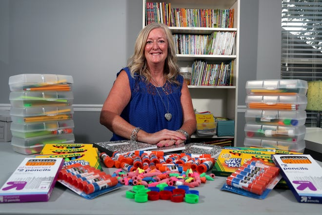 Tia Gannon, School Rocks Party Box founder and director, sits with donated school supplies to be delivered to school children in need as part of her nonprofit's mission. She is shown Sept. 13 at her Dublin home, where she and other group members and volunteers package the school supply packets.