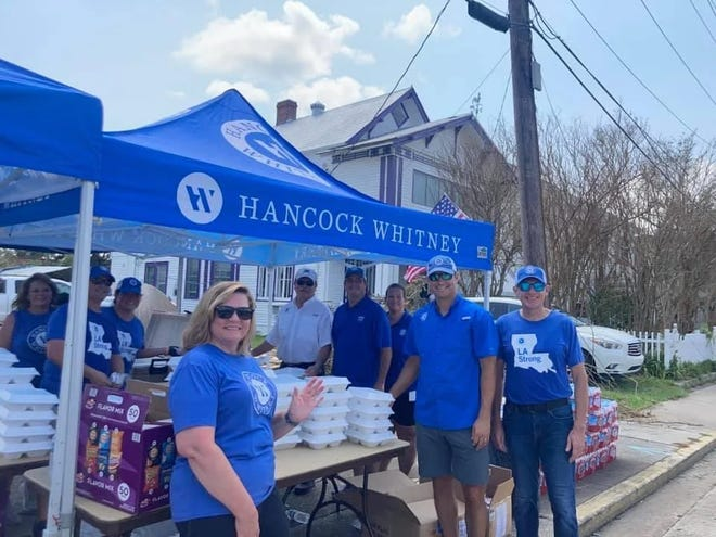 Hancock Whitney bank employees and volunteers prepare food for storm victims after Hurricane Ida.