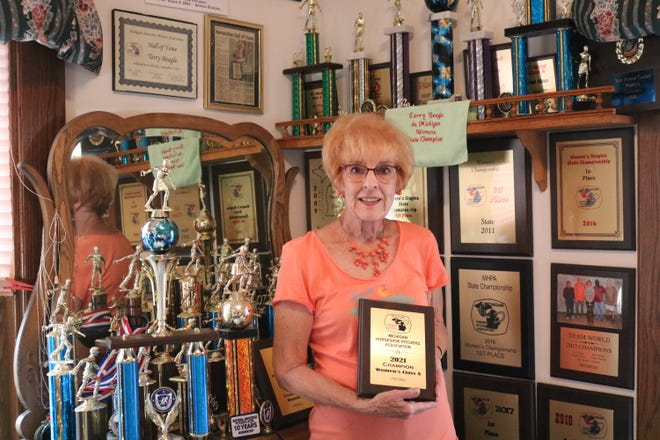 Terry Beagle stands in front of her competitive horseshoe pitching accolades while holding her Michigan Horseshoe Pitchers Association trophy for winning this year's state competition in Class A, an accomplishment as it was her 10th state championship for the resident of Clayton.