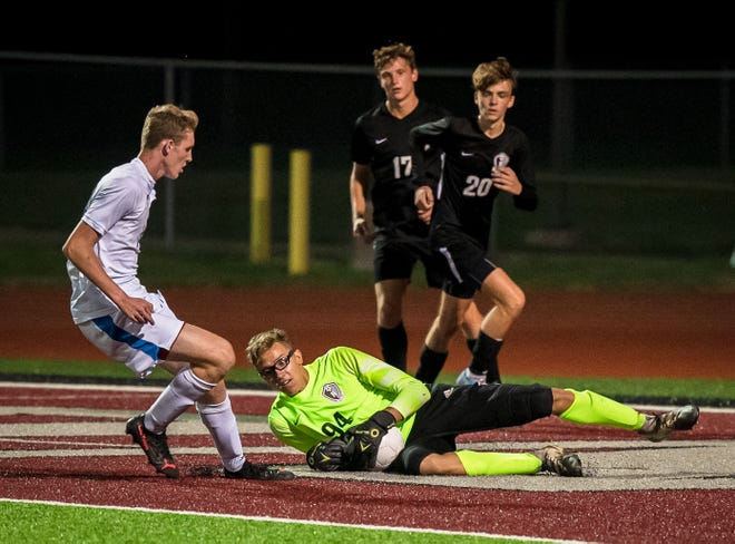 Lee's Summit North goalkeeper Jackson Reynolds (94) makes a save on a shot by Blue Springs South's Aiden Wahrenbrock, left, in Monday's game at North. Despite 11 saves by Reynolds, the Broncos fell 3-1 to the Jaguars.