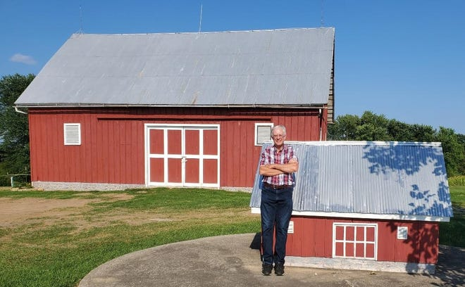 Jon Finney stands in front of his model barn that is 15% to scale of the original barn.