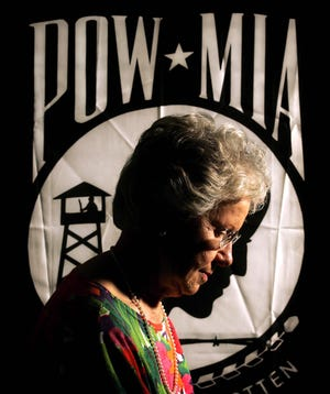 Mary Helen Hoff, then 73, posed in 2004 before the POW-MIA flag that she inspired in the early 1970s after her husband Mike, a Navy pilot, went missing in action in Laos in 1970. He was later presumed killed in action.