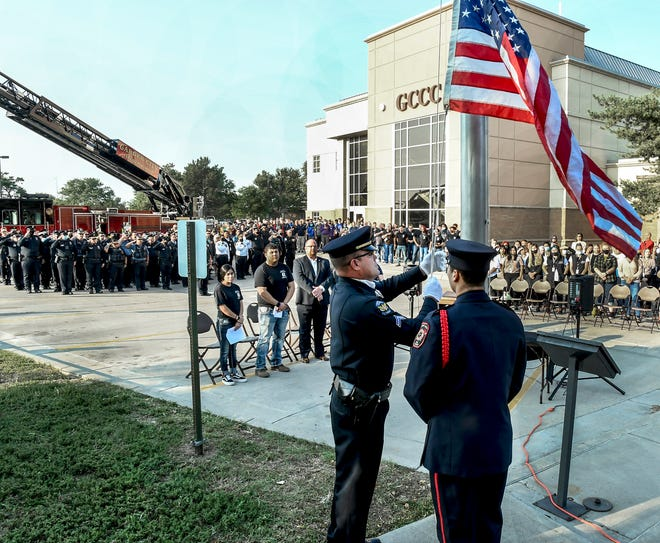 Members of the Garden City Fire Department's Honor Guard raise the flag to half staff Monday at Garden City Community College as first responders, GCCC staff and students as well as community members look on during a Sept. 11, 2001 remembrance ceremony.  With Sept. 11 falling on the weekend, the ceremony was held on Monday so more individuals could attend.