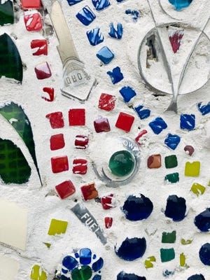 Mosaic art underway on riverwalk wall uses any trinkets the makers can find to create the multifaceted pieces.