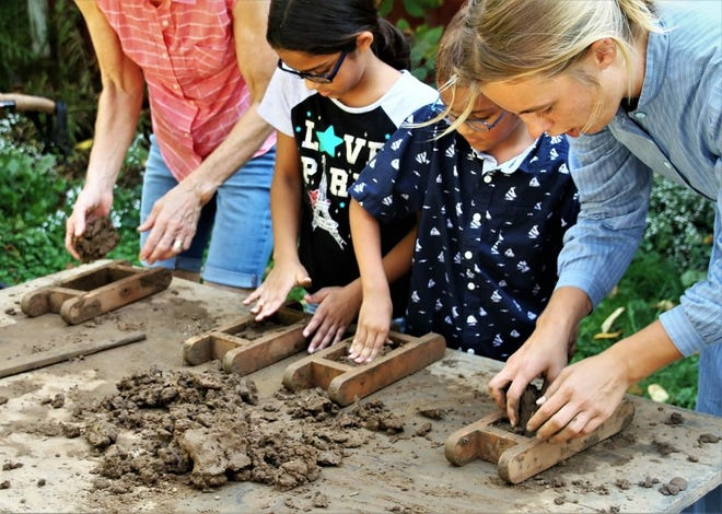 Festival goers try their hand at brick making
