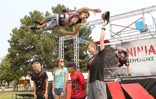 Jake the Snake flies over volunteers from the crowd as he grabs the hat from Paul Hawkinson during the Ninja Experience show at the Kansas State Fair Friday afternoon, Sept. 10, 2021.