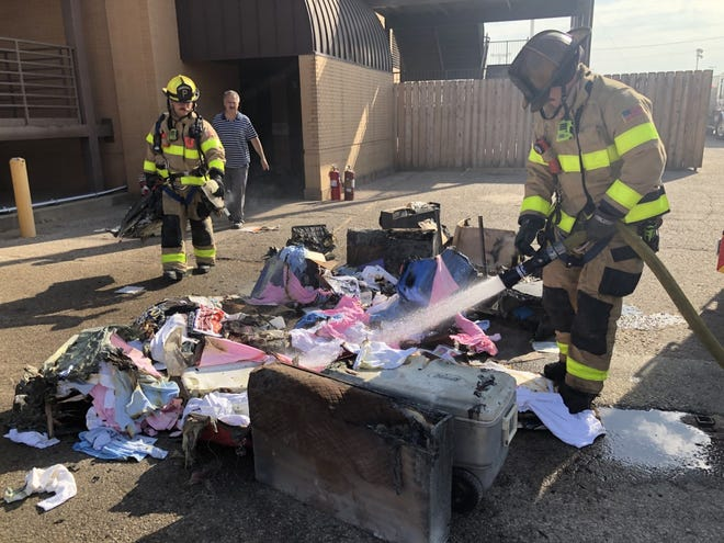 A Hutchinson firefighter sprays clothing and equipment pulled from a booth under the Kansas State Fair grandstand Tuesday morning after an overloaded extension cord caught items in the booth selling T-shirts and leather goods on fire. The fire forced the temporary shutdown of several other food and merchandise vendors.